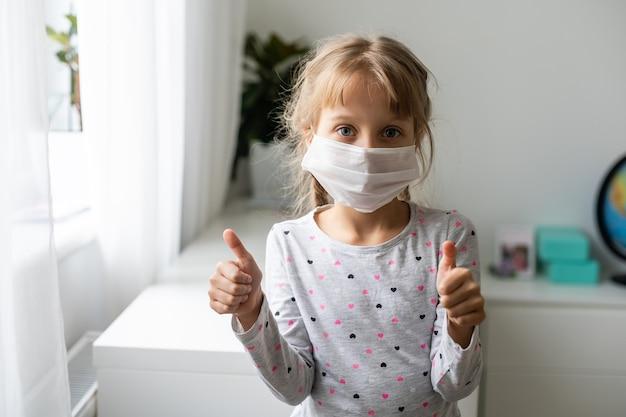 Ребенок в маске - защита от вируса гриппа. маленькая кавказская девочка в маске для защиты pm2.5. биологическое оружие. ребенок на сером фоне с копией пространства. эпидемия, пандемия.