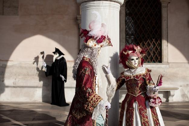 ヴェネツィアの仮面舞踏会で華やかな衣装を着た仮面のカップルが、ヴェネツィアのサンマルコ広場近くの石の壁に立っています。