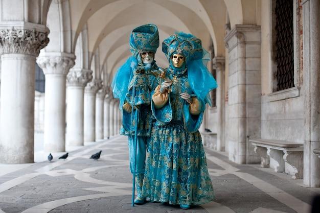 ヴェネツィアの聖マルコ広場の近くに立つヴェネツィアの仮面舞踏会で華やかな衣装を着た仮面のカップル