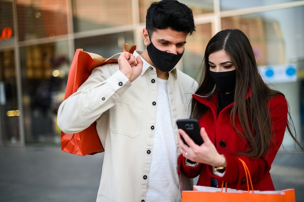 Masked couple shopping in a street market and using a smartphone wearing masks, covid coronavirus concept