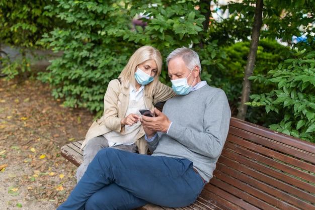 Пара в маске с помощью мобильного телефона вместе в парке во время пандемии коронавируса