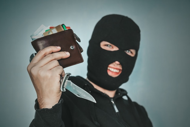 Преступник в маске на черном фоне ухмыляется, глядя на зрителя и показывая кошелек в руке. злоумышленник рад украденному кожаному кошельку. довольный грабитель после кражи. воровская природа