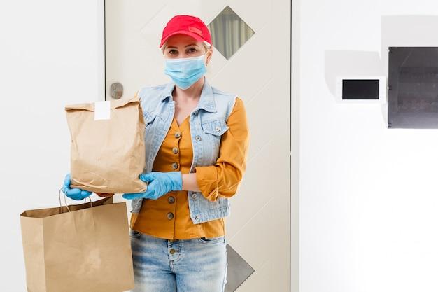 マスクされた配達の女性は、ウイルスの発生、コロナウイルスのパニックおよびパンデミックの間に食物を配達します。