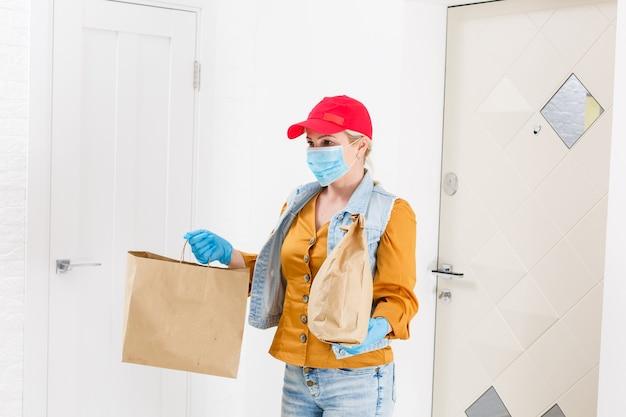 仮面分娩の女性は、ウイルスの発生、コロナウイルスのパニック、パンデミックの際に食べ物を届けます。