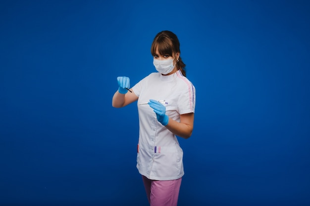 A masked doctor holds a scalpel in his hands on a blue background