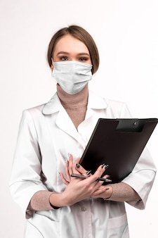 Masked doctor looking at the camera and holding a tablet