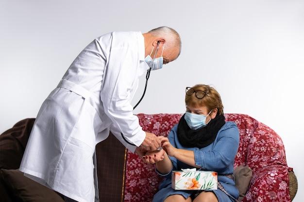 가면을 쓴 의사가 집에서 건강 검진을받는 동안 노인 여성의 맥박을 측정합니다.