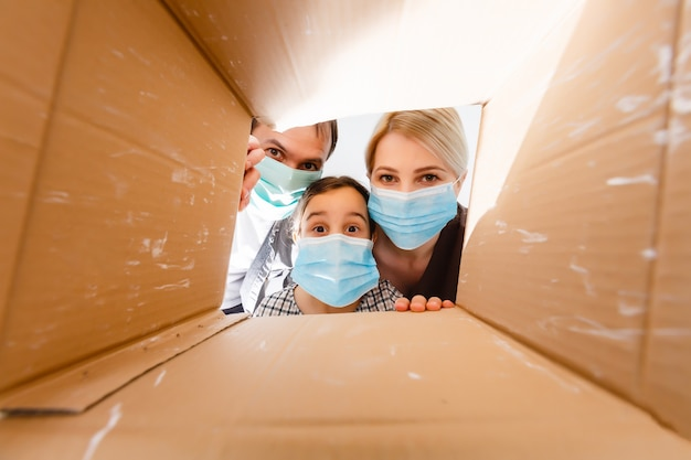 Masked family looking into the box. food and goods contactless delivery during coronavirus quarantine for isolated people.