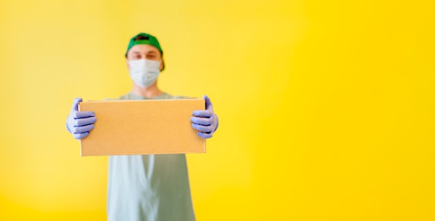 Masked food delivery man. the courier is holding a box in rubber gloves and a suit. green shape, yellow background