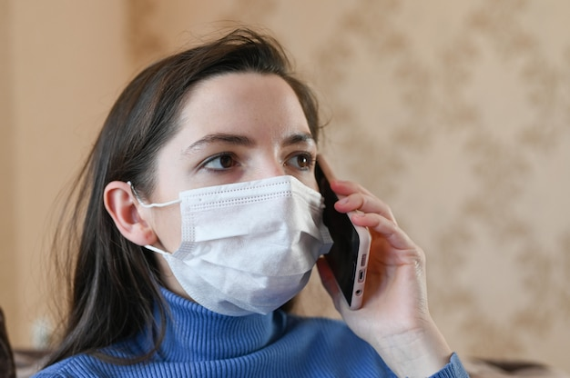 The masked girl calls the doctor on the phone. first signs of coronavirus