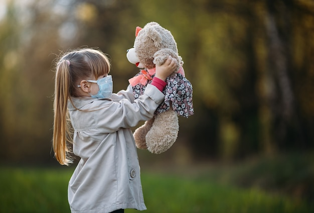 Masked girl holding a bear in the park.