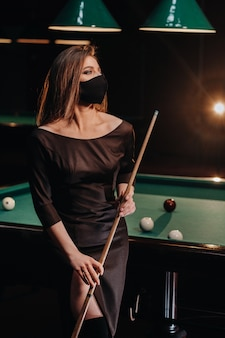 Masked girl in a pool club with a cue in her hands.