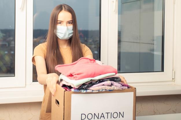 Девушка в маске с ящиком для пожертвований с одеждой для бедных
