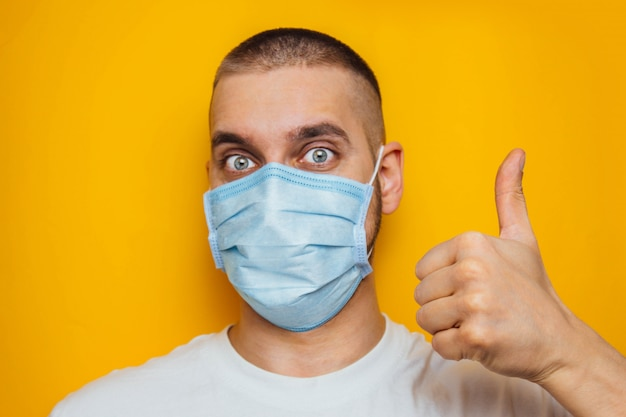 Masked guy looks at the camera and shows a thumbs up gesture. against quarantine. sit at home. cold, flu, virus, epidemic concept.