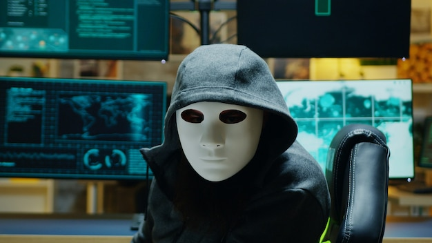 Masked hacker in his apartment looking into the camera while stealing online information.