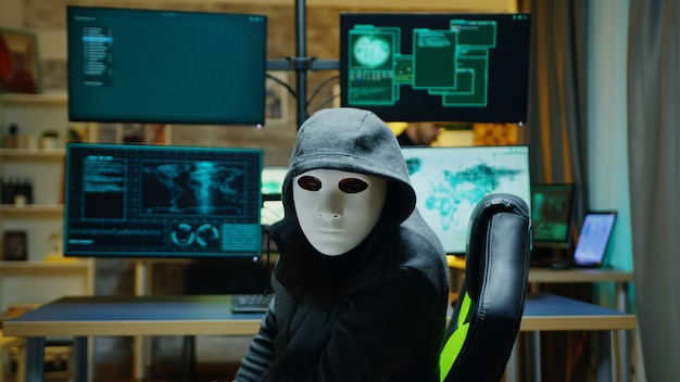 Hacker mascherato che indossa una felpa con cappuccio per nascondere la sua identità. criminale di internet.