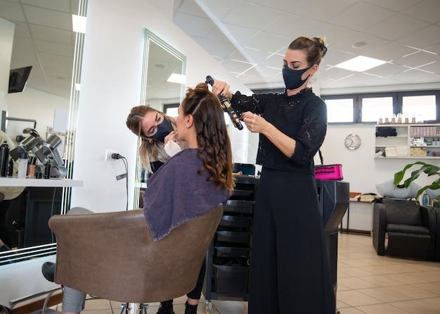 髪に取り組んでいるマスクされた美容師と顧客を構成し、コロナウイルスとファッションコンセプトの間に働きます