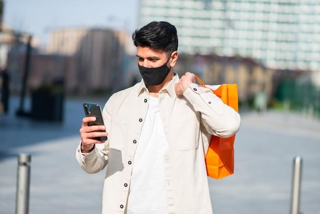 スマートフォン、covid、コロナウイルスの概念を使用しながら買い物袋を運ぶ仮面の男