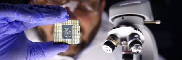 Masked man examines a microcircuit near microscope. high performance and unique ability to combine technology into solutions. installing or replacing motherboard. recommendations for proper operation