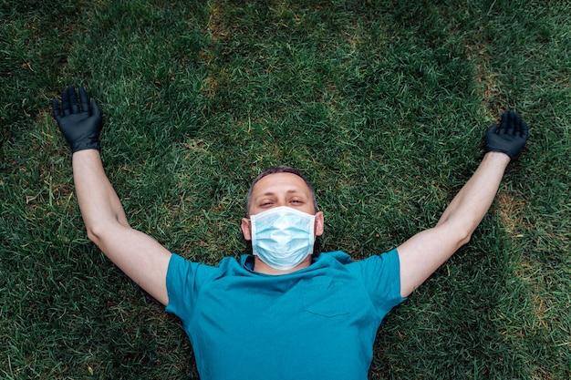 草の上に横たわって、屋外で仮面の男