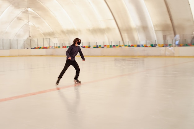A masked man skates on ice
