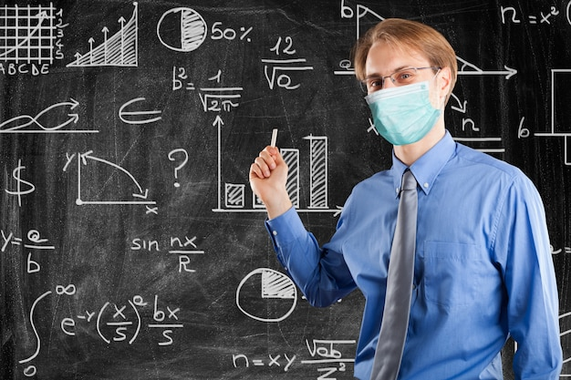 Masked man writing on a blackboard
