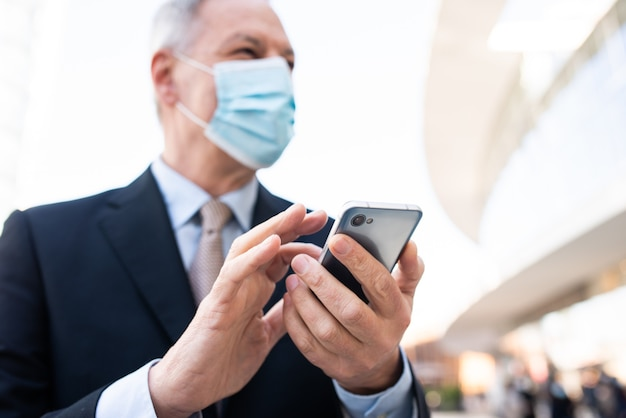 彼のスマートフォンの屋外、covid、コロナウイルスの概念を使用してマスクされた成熟したビジネスマン