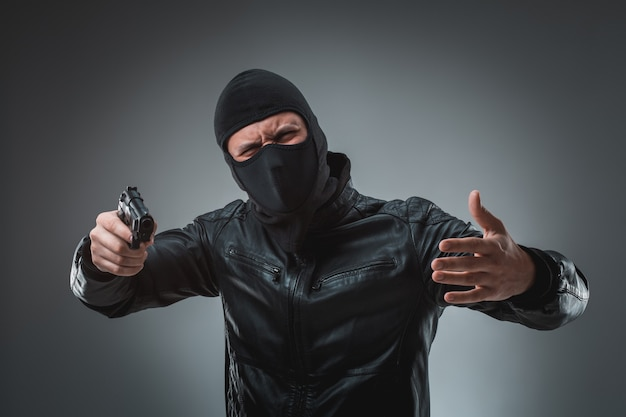 Masked robber with gun, looking into the camera.