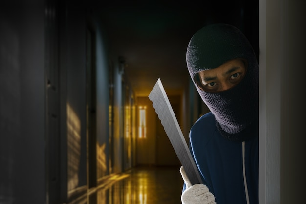 Masked robber with knife hiding behind the door