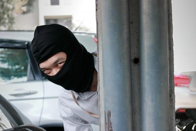 Masked thief hiding behind a pole before burglary. car thief criminal concept.