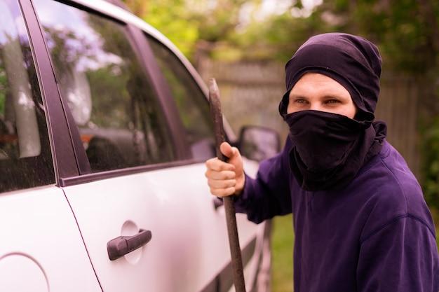 Вор в маске стоит возле машины и пытается разбить окно перекладиной