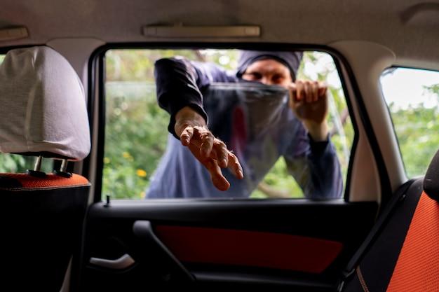 Вор в маске разблокирует и откройте окно машины, чтобы украсть собственность