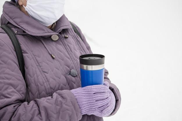 코로나 바이러스 전염병 기간 동안 겨울 날 뜨거운 음료와 함께 열 컵을 들고 마스크 된 여자.