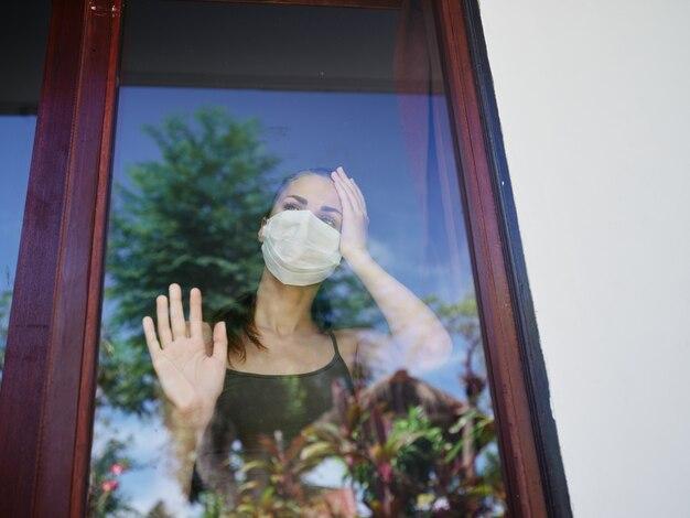 窓の検疫禁止に寄りかかっている仮面の女