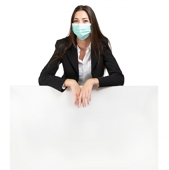 Masked woman leaning on a sign, advertisement during coronavirus pandemic, isolated on white