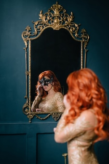 マスクされた女性は彼女の反射を鏡で見る
