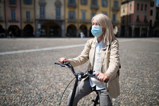 Masked woman riding her e-bike in a city during coronavirus pandemic