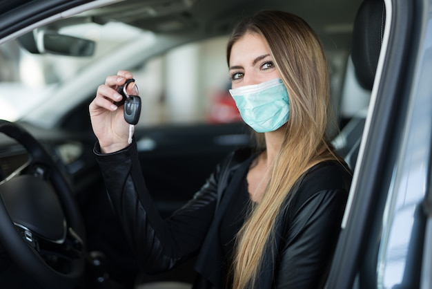 Masked woman showing the key of her new car in a car dealer saloon