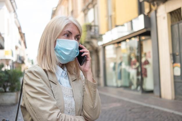 街の通りを歩きながら電話で話している仮面の女