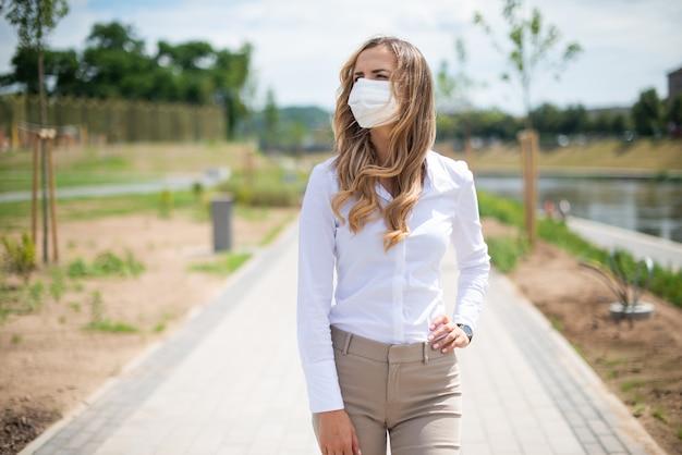 Женщина в маске гуляет в городском парке во время чрезвычайной ситуации с коронавирусом