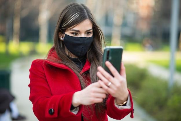 コロナウイルスの緊急時にスマートフォンを使用しながら都市公園を歩いている仮面の女性