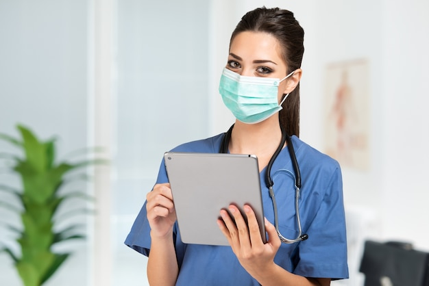 Masked young nurse doctor using a tablet
