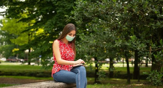 公園でタブレットを使用してマスクされた若い女性