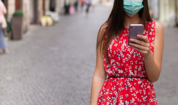 Masked young woman walking in a city while using her mobile phone