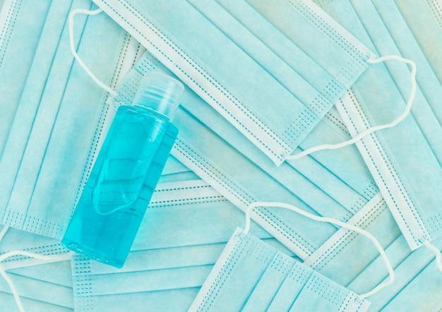 マスクと青色の背景に消毒ゲルのボトル。