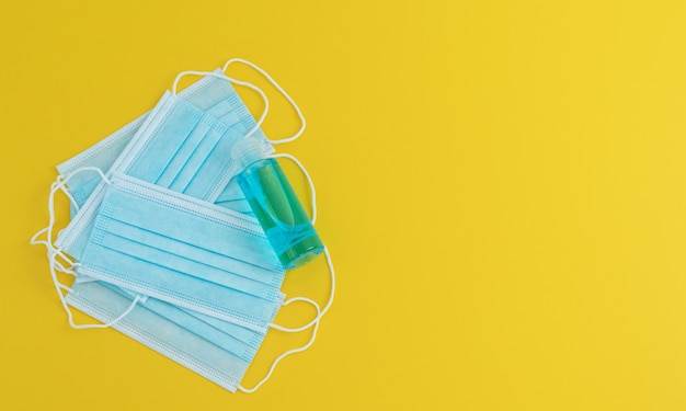 Masks and bottle of disinfectant gel on a yellow background.