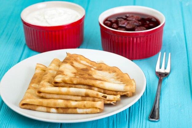 Масленица и масленица. блюдо, полное русских традиционных блинов со сметаной на блюдце на синем фоне