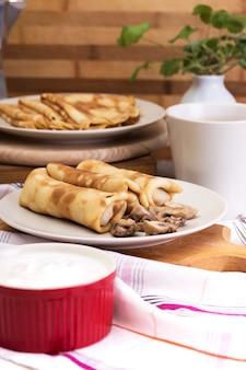 Масленица и масленица. блюдо из русских традиционных блинов со сметаной на блюдце