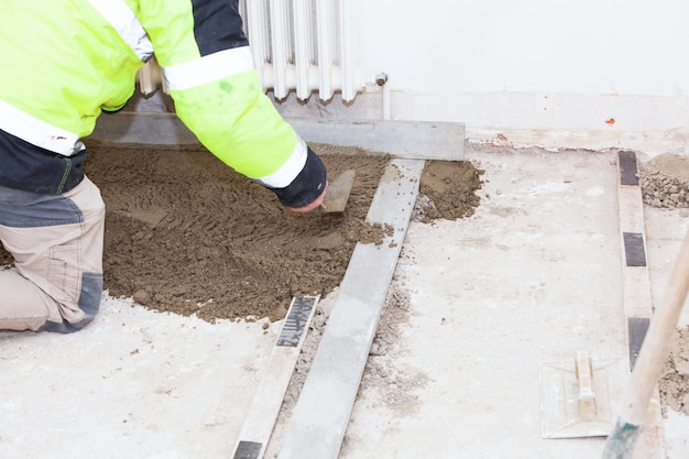Mason building a cement screed