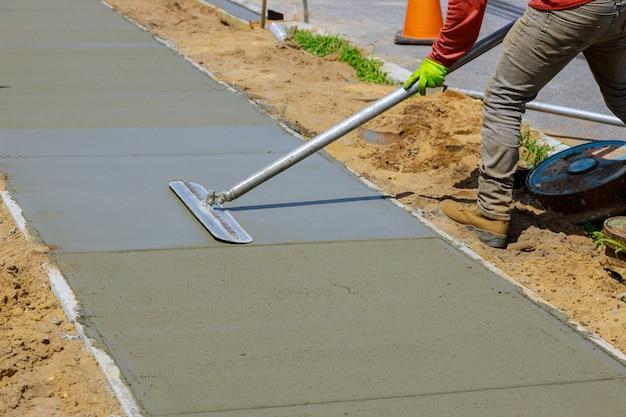 Mason building a screed coat cement a laborer floats a new concrete sidewalk